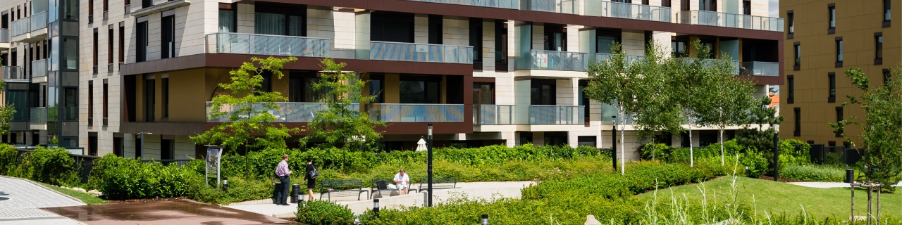 Image of low-rise apartment, green space and people enjoying the outdoors.