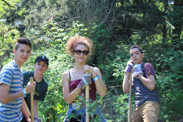 Youth taking a quick break from removing invasive species at Esquimalt's Highrock Park during Earth Day celebrations.